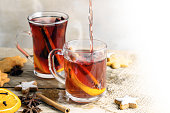 mulled wine in two glass mugs with Christmas cookies and spices like orange slices, cloves, star anise and cinnamon on a bright rustic table, background fades to white, copy space, selected focus, ver