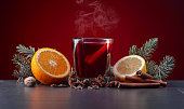 Mulled wine with spices , orange and lemon on a black table. Christmas concept .
