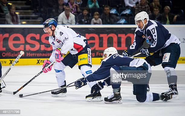 TJ Mulock of the Eisbaeren Berlin Dominik Tiffels and Thomas Oppenheimer of the Hamburg Freezers during the game between Hamburg Freezers and...