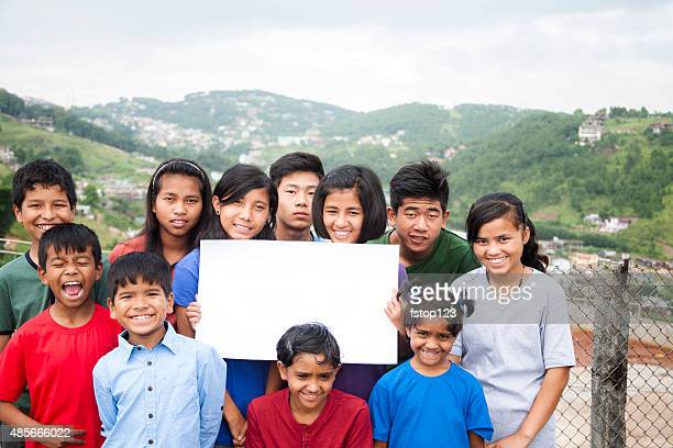 Mult-ethnic, large group of children hold blank sign outdoors.