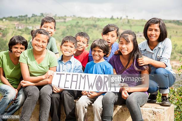 Mult-ethnic, large group of children hold 'teamwork' sign outdoors.