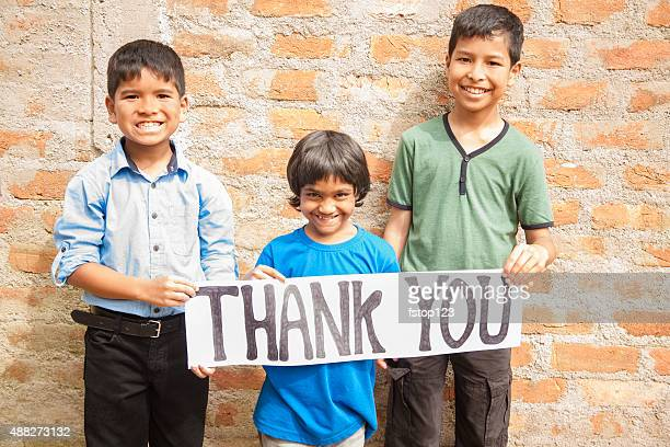 Mult-ethnic, small group of children hold 'Thank You' sign outdoors.