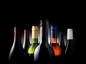group shot of seven wine bottles, backlit on black background, can be used for wine list or similar