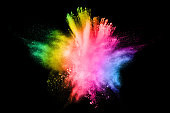 Multi color powder explosion on black background. Mauve color cloud. Color dust splash. Freeze motion of paint Holi.