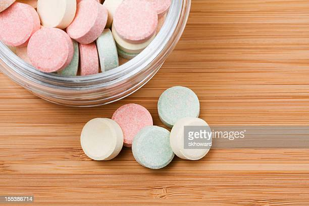 Multi Colored Antacid Tablets on Wood