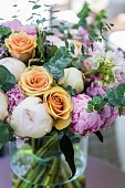 Vertical colour close-up image of beautiful bouquet of multi colored roses arranged in vase.