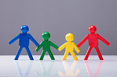 Multi Colored Human Figures Standing Together In A Row On White Desk