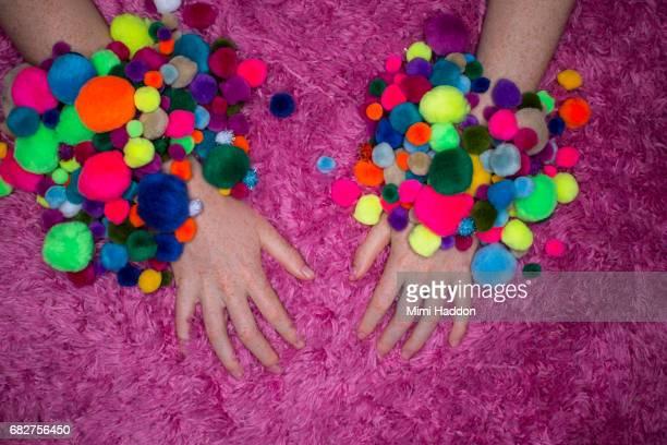 Multi colored pom pom bracelets on hands