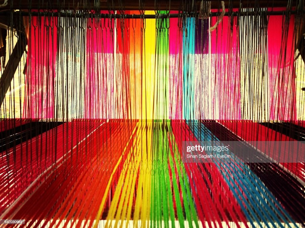 Multi Colored Threads Hanging On Machine