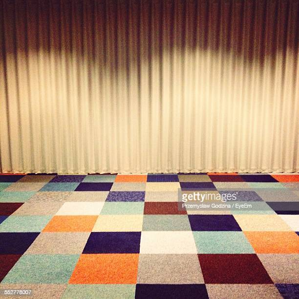 Multi Colored Tiled Floor Against Curtains At Office