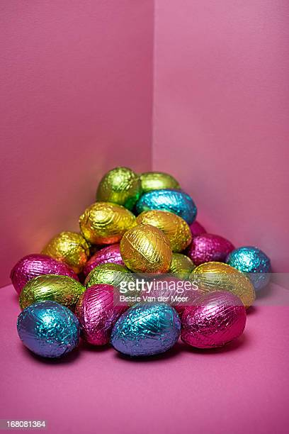 Multi coloured easter eggs on a pink background.