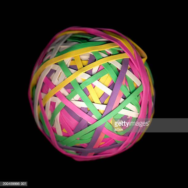 Multi coloured eleastic band ball against black background, close-up