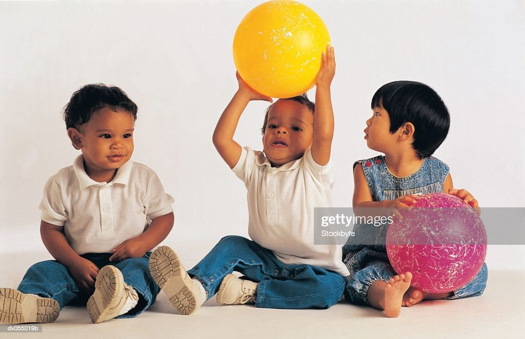 Multi cultural children playing with balloons : Stock Photo