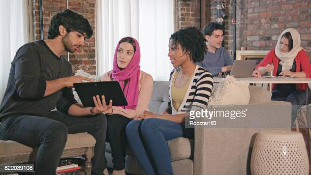 Multi Ethnic Adults Interact with Digital Tablet