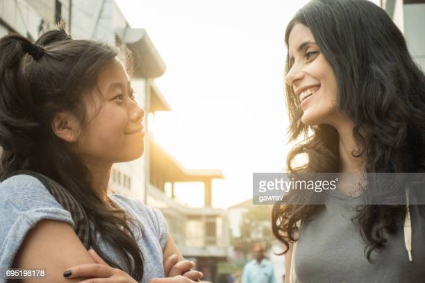 Multi ethnic Asian female friends talking together face to face.