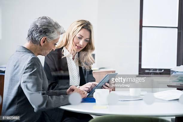 Multi ethnic businesswomen using tablet in modern office