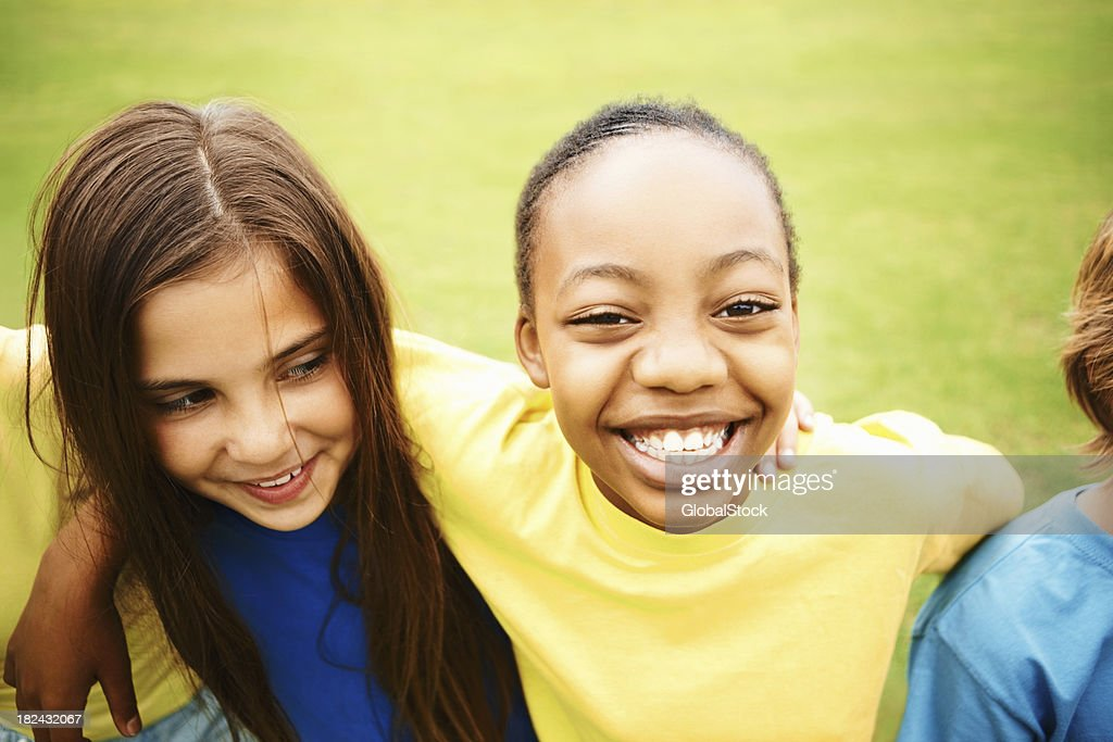 Multi ethnic children enjoying on the lawn : Stock Photo