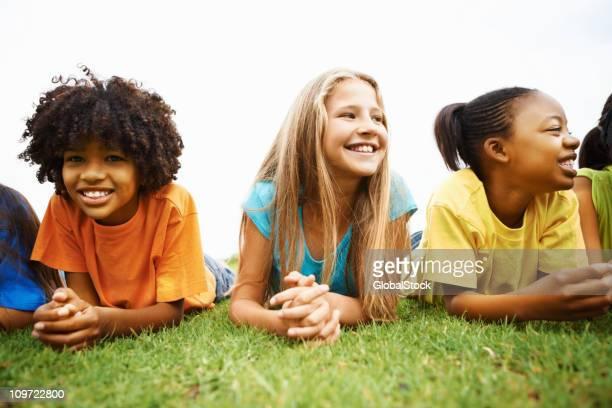 Multi ethnic children lying on grass