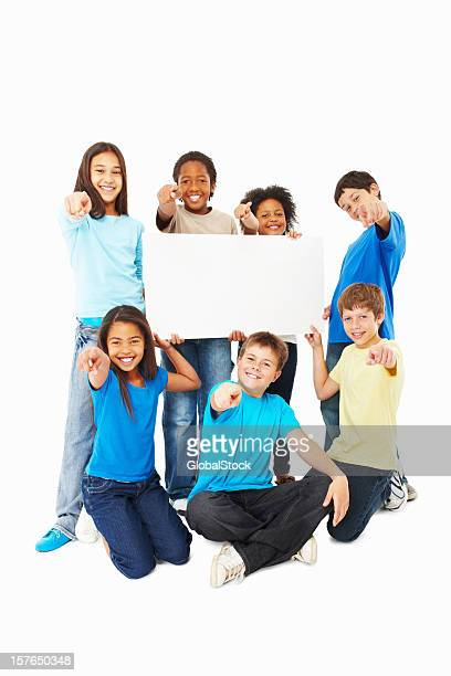 Multi ethnic children with a blank board pointing towards you