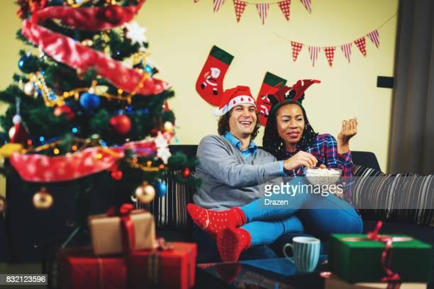 Multi ethnic couple in UK celebrating Christmas and watching TV