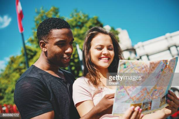 Multi ethnic couple looking at the map of London