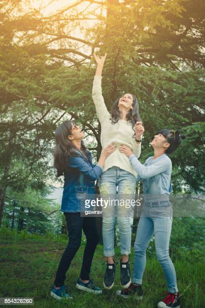 Multi ethnic female friends doing fun together in woods.