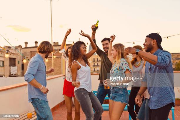 Multi ethnic friends dancing at the rooftop party