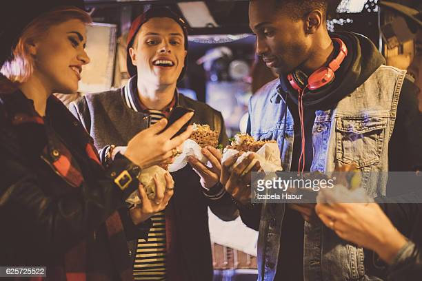 Multi ethnic friends eating burgers in pub