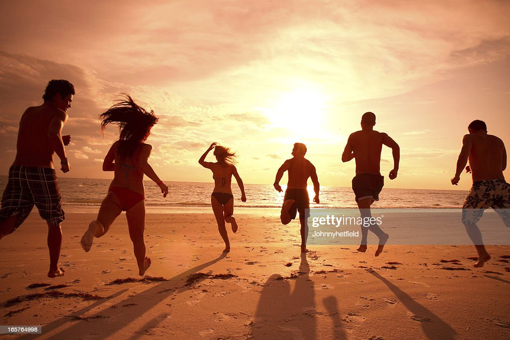 Multi ethnic friends running to the ocean : Stock Photo