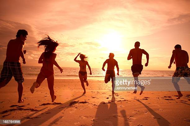 Multi ethnic friends running to the ocean