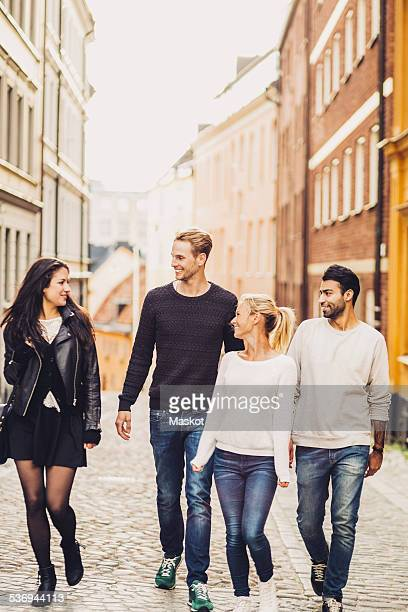 Multi ethnic friends walking on city street