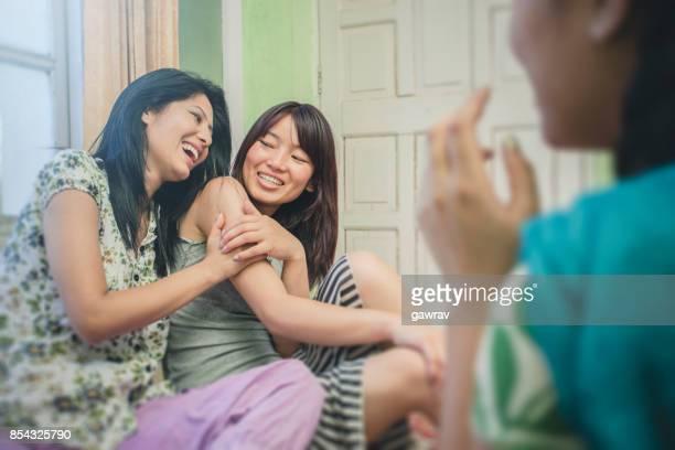 Multi ethnic girls in fits of boisterous burst of laughter.