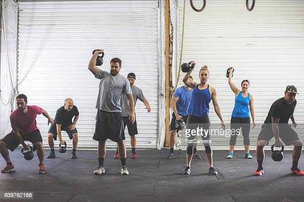 Multi ethnic group doing a kettlebell workout together