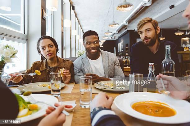 Multi ethnischen Gruppe von Freunden essen Abendessen in einem restaurant