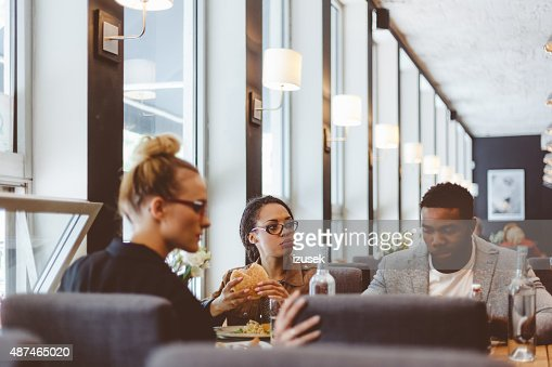 Multi ethnic group of friends having lunch in a restaurant