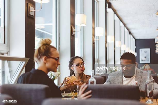 Multi ethnique groupe d'amis ayant un déjeuner dans un restaurant