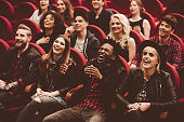 Multi ethnic group of young people in the cinema or theater, watching, laughing.