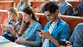 Multi Ethnic Group of Students Using Smartphones During the Lecture. Young People Using Social Media while Studying in the University.