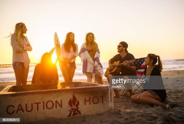 Grupo étnico multi de la gente joven, pasar viendo atardecer de tiempo en la playa en San Diego, tocando la guitarra y se calienta por el fuego