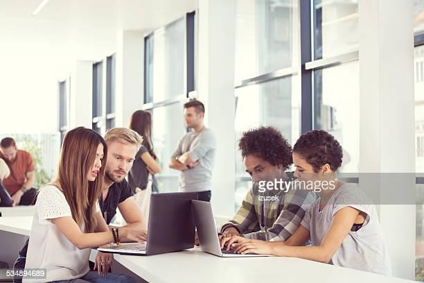 Multi étnica alunos trabalhando juntos em computadores portáteis na universidade