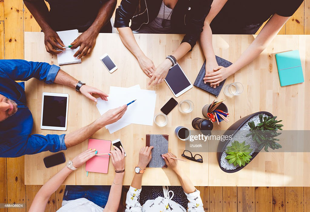 Multi ethnic team brainstorming, high angle view on the table : Stock Photo
