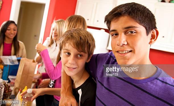 Multi etnico giovani in cucina rendendo il pranzo a scuola. Fratelli.