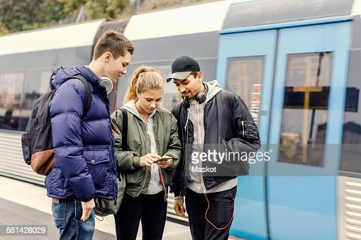 Multi ethnic university students using mobile phone at subway station