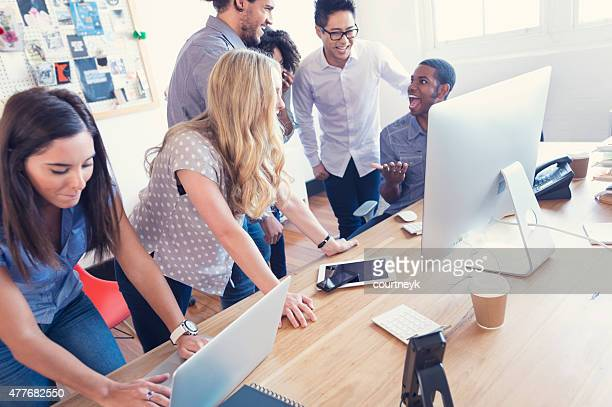 Multi ethnic young business team working on computers.