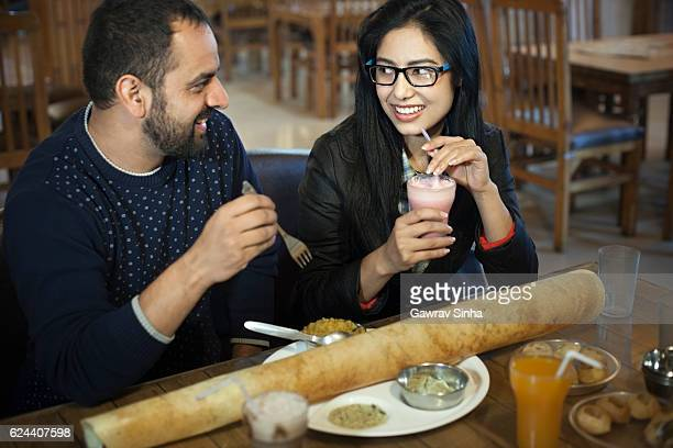 Multi ethnic young couple eating south Indian food at restaurant.