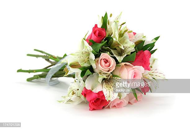 Multi flower bouquet tied with white ribbon lying on side