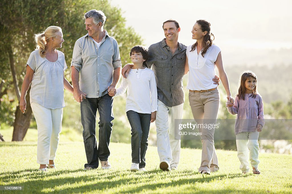 Multi generation family holding hands and walking in the park : Stock Photo