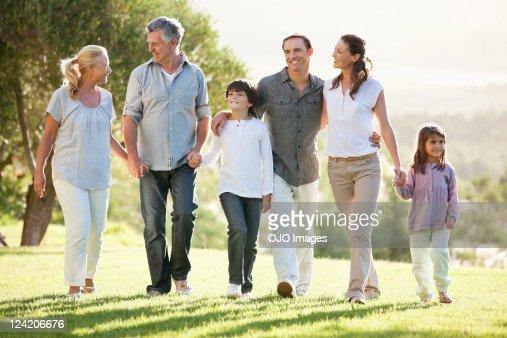 Multi geração família segurando as mãos e andar no parque : Foto de stock