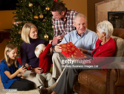 Multi Generation Family Opening Christmas Presents In Front Of Tree : Foto de stock