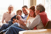 Multi Generation Family Sitting On Sofa With Newborn Baby Smiling